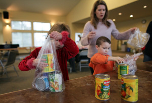 Volunteers, including Harmony and Evan Coppi, pack food during a Healthy HIP Packs Program packing party. (seattlepi.com photo, used with permission)