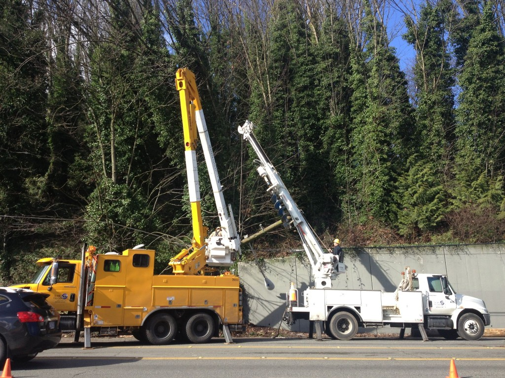 A City Light crew works to right a large power pole knocked down on Lake City Way.