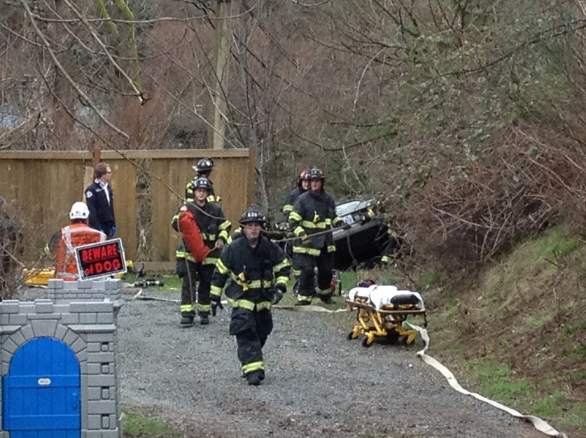 Firefighters work to remove a man trapped in a car on the edge of Thornton Creek ravine.