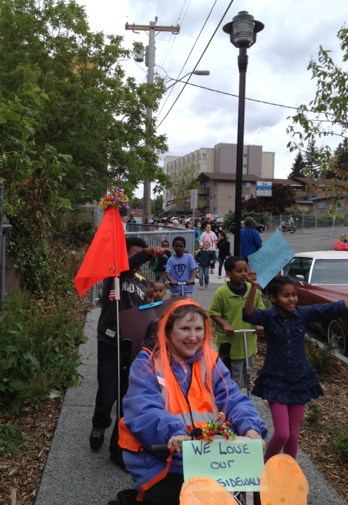 A parade of happy residents make their way along a new sidewalk on 33rd Avenue NE.