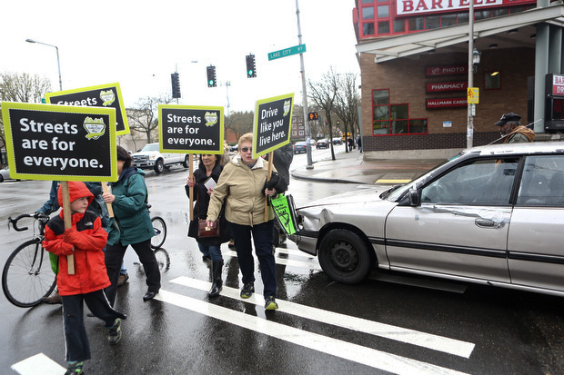 Marchers are pushed to the edge of the crosswalk by a car. (LCL photo)