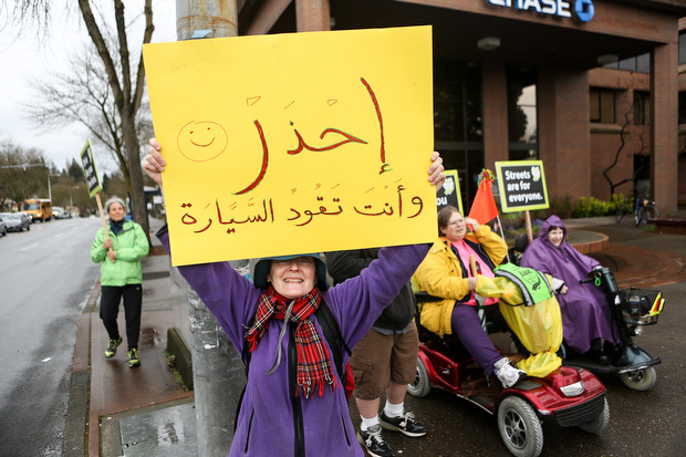 A sign written in Arabic is held up. (LCL photo)