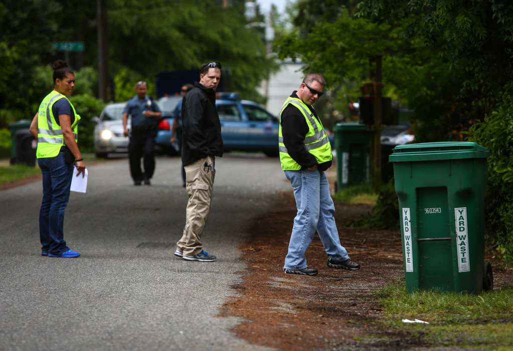Seattle Police investigators look over the scene where a dark sedan hit a woman pushing a baby stroller on 19th Avenue Northeast in the Olypmic Hills neighborhood of Seattle. The driver fled the scene. The neighborhood is one of many areas in north and south Seattle that does not have sidewalks and pedestrians are forced to walk in the street. Photographed on Friday, May 23, 2014. (Joshua Trujillo, seattlepi.com)